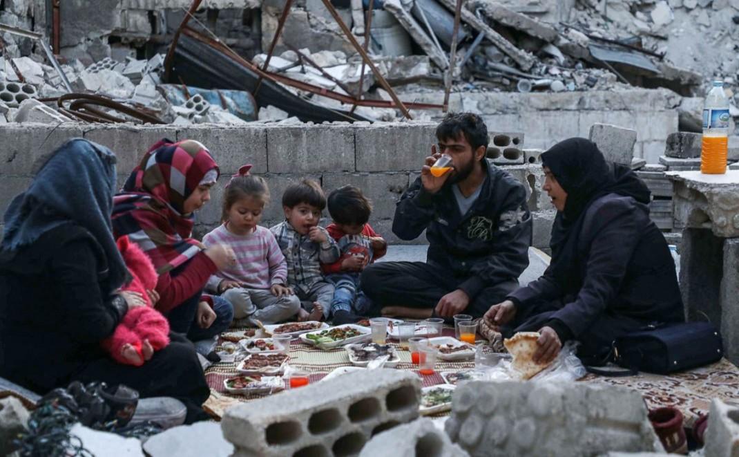 Сирийская семья Тарека Абу Зиада из города Ариха разгавляются среди обломков своего разрушенного дома