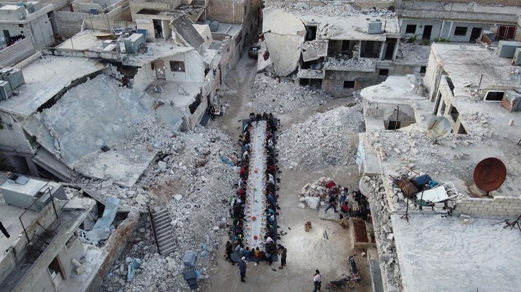 Сирийцы сидят среди развалин своего разрушенного квартала во время ифтара, организованной местной благотворительной организацией